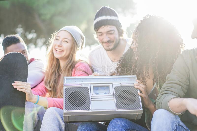 Happy friends listening music in skate park with back sun light - Young people having fun together - Youth and friendship concept royalty free stock photography
