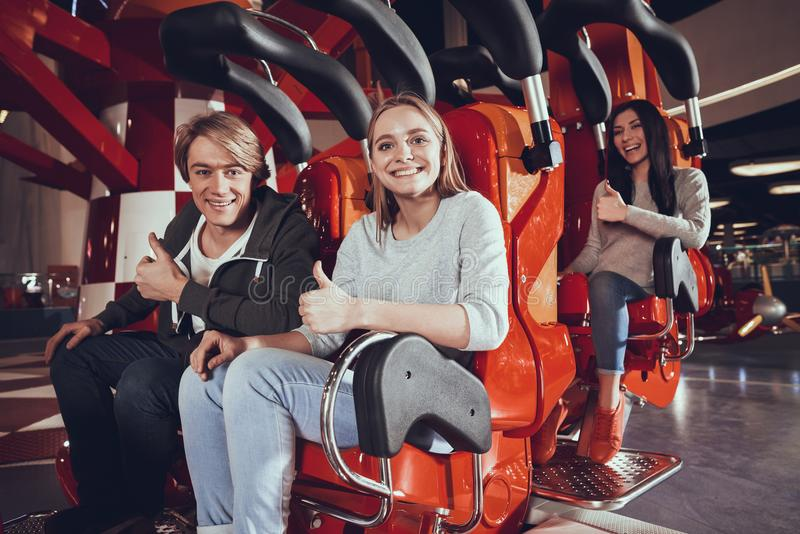 Happy friends are looking at camera in amusement park. royalty free stock image