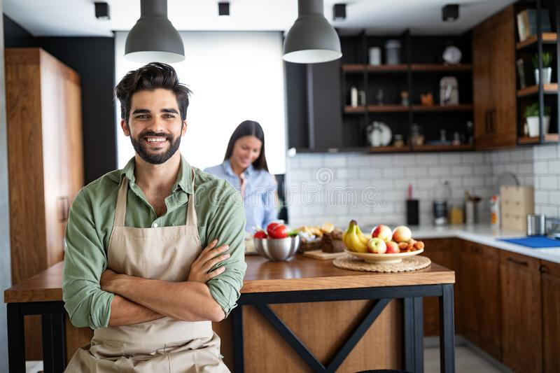 Happy young friends loving couple chefs on the kitchen cooking. stock photography