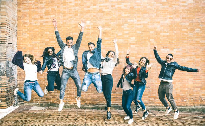 Happy friends millennials jumping and cheering against brick wall stock image