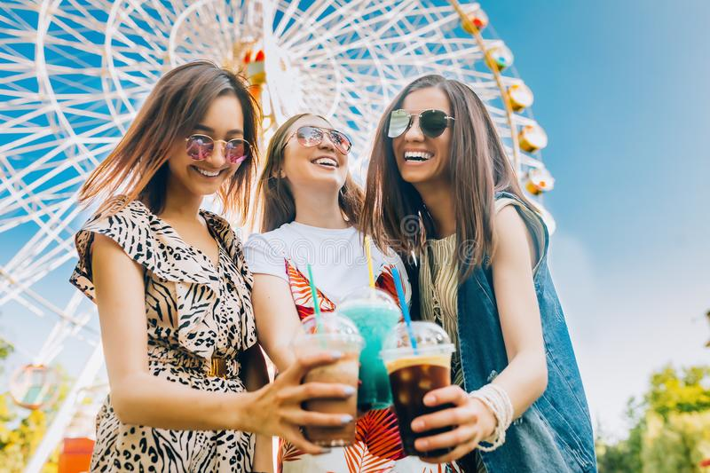 Summer lifestyle portrait multiracial women enjoy nice day, holding glasses of milkshakes. Happy friends inin front of stock photography