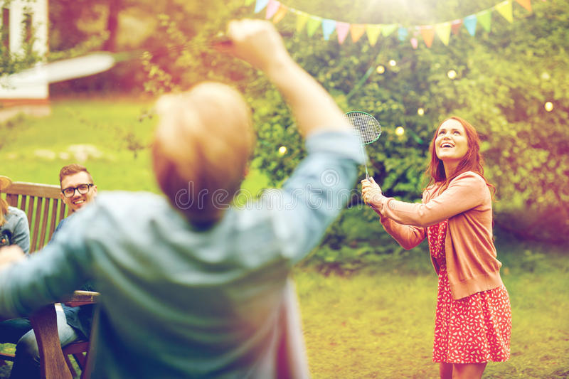 Happy friends playing badminton at summer garden stock image