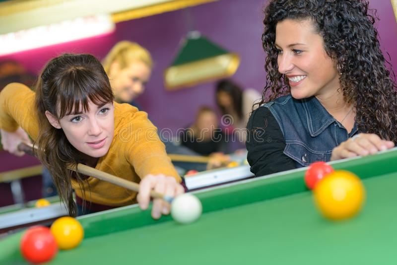 Happy friends playing billiards stock image