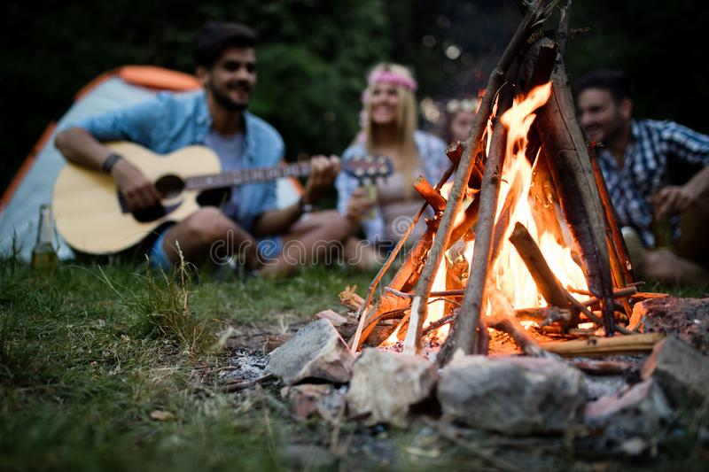 Friends playing music and enjoying bonfire in nature. Happy friends playing music and enjoying bonfire in nature royalty free stock photography