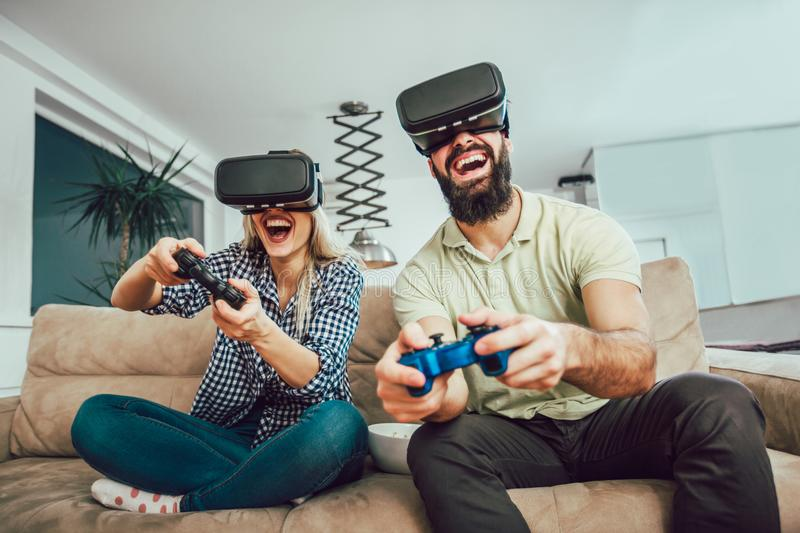 Happy friends playing video games with virtual reality glasses. Young people having fun with new technology console online stock images