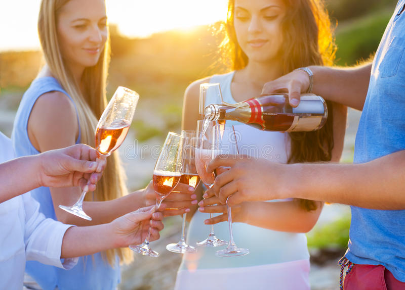 Happy friends pouring champagne sparkling wine into glasses outdoors at a beach royalty free stock images