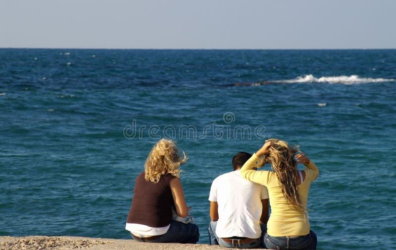 Happy friends on a sea shore stock image
