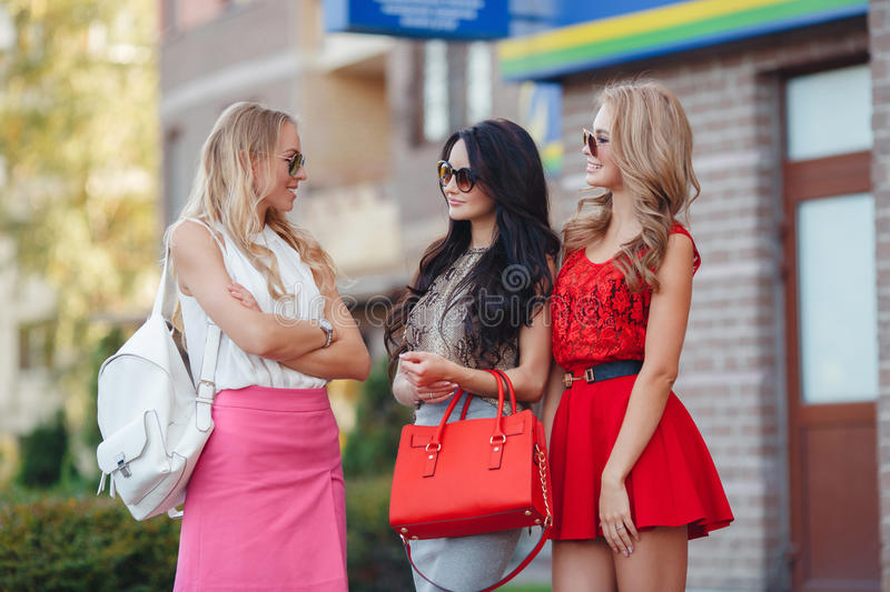 Happy friends with shopping bags ready to shopping. Three happy girlfriends, two blondes and the brunette, in sun glasses, are dressed in easy summer dresses stock images