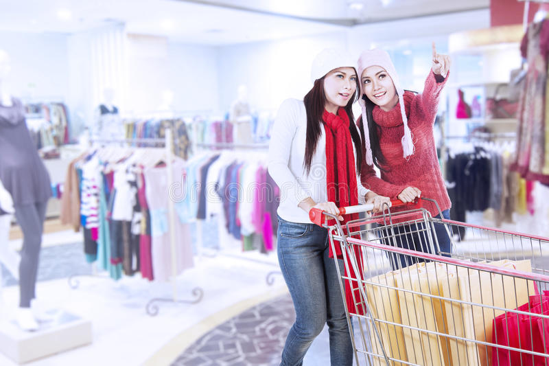 Happy friends shopping with trolley at the mall. Two friends are shopping with trolley at the mall royalty free stock image