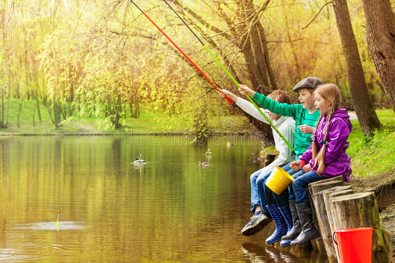 Happy friends sit fishing together near pond stock photography