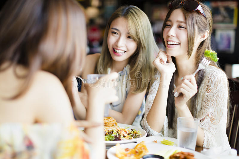 Happy friends sitting and chatting in restaurant royalty free stock photography
