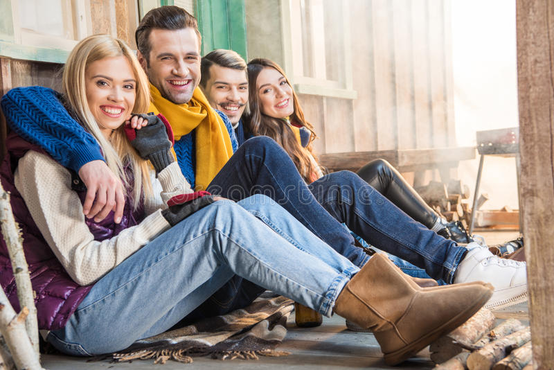 Happy friends sitting together and looking to camera stock photography