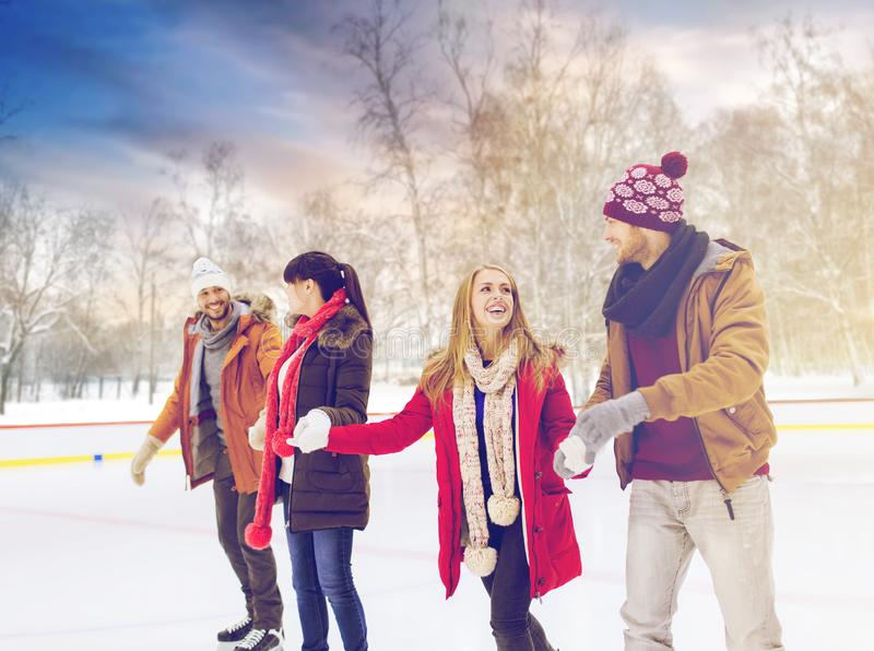 Happy friends on skating rink outdoors. People, friendship and leisure concept - happy friends on skating rink outdoors stock photography