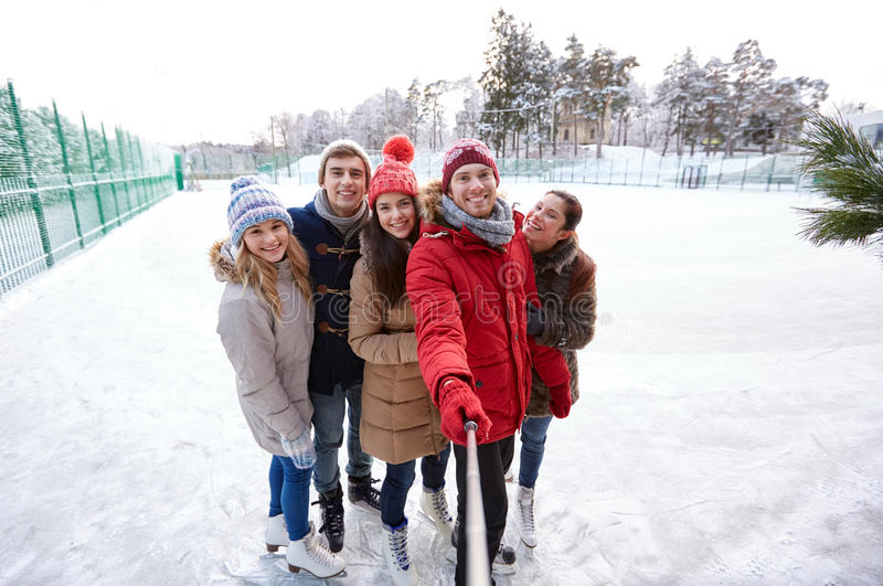 Happy friends with smartphone on ice skating rink. People, friendship, technology and leisure concept - happy friends taking picture with smartphone selfie stick royalty free stock photos