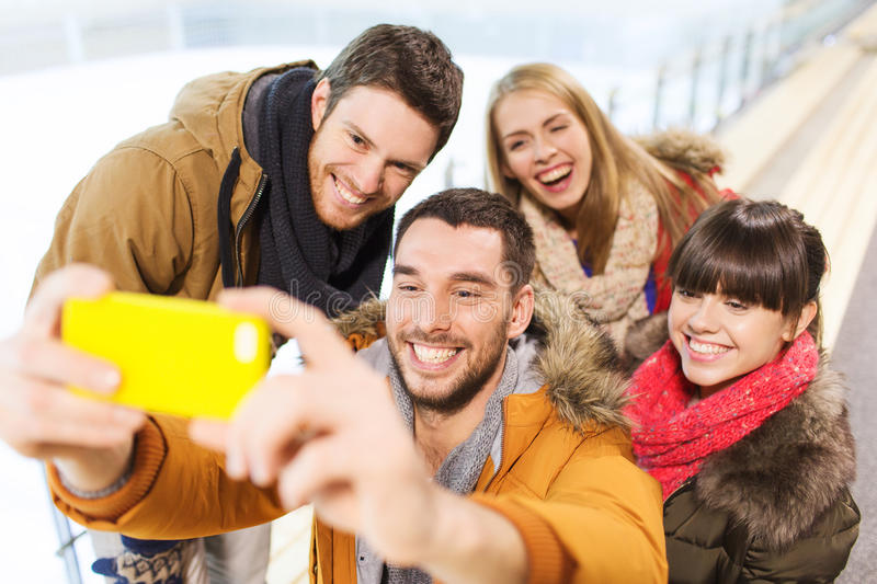 Happy friends with smartphone on skating rink. People, friendship, technology and leisure concept - happy friends taking selfie with smartphone on skating rink royalty free stock photo