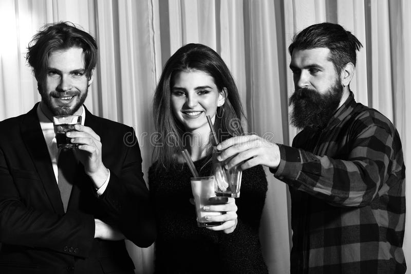 Happy friends smiling and clinking glasses with cocktails and alcohol. Happy friends, pretty girl and two bearded men, hipsters with beard, in red plaid shirt stock images