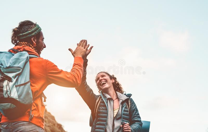 Happy friends stacking hands while doing trekking excursion on mountain - Young tourists walking and exploring the wild nature royalty free stock photos