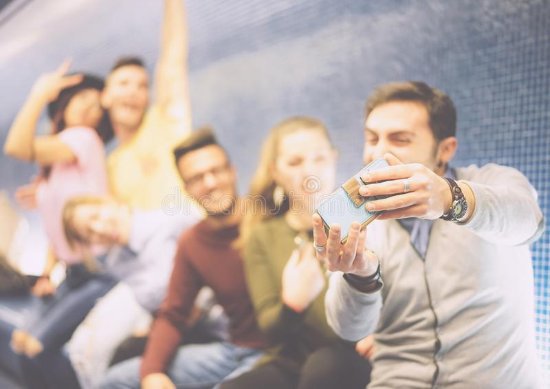 Happy friends taking a photo selfie using their mobile smartphone camera sitting in a underground royalty free stock image