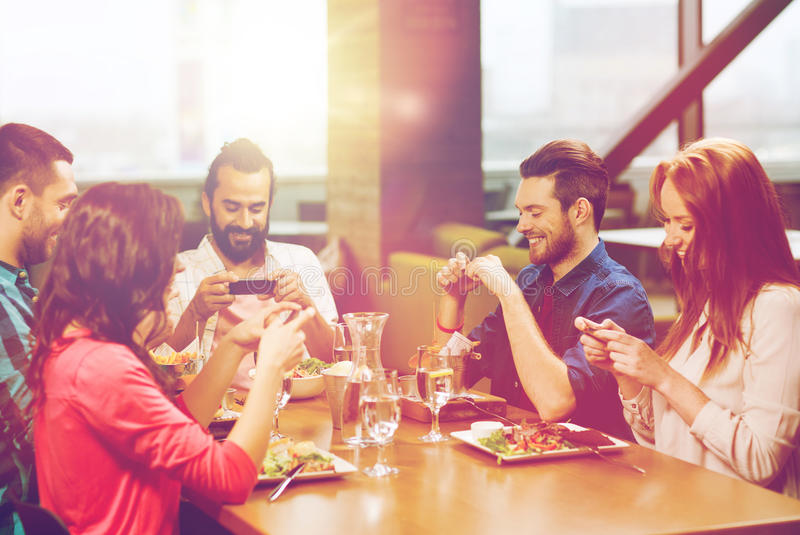 Happy friends taking picture of food at restaurant stock image