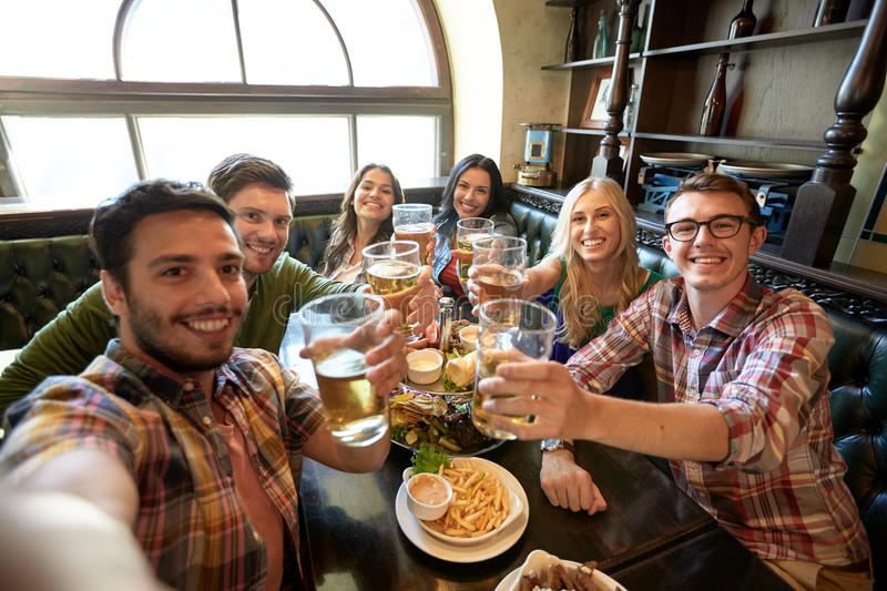 Happy friends taking selfie at bar or pub royalty free stock image
