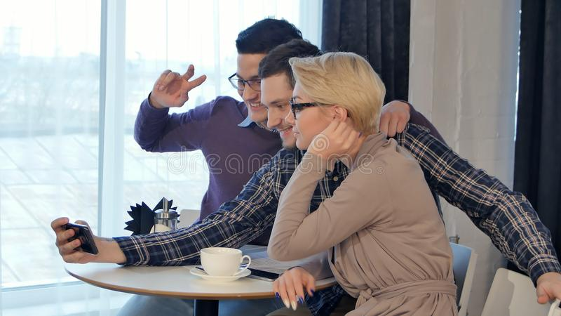 Happy friends taking selfie in cafe royalty free stock photography
