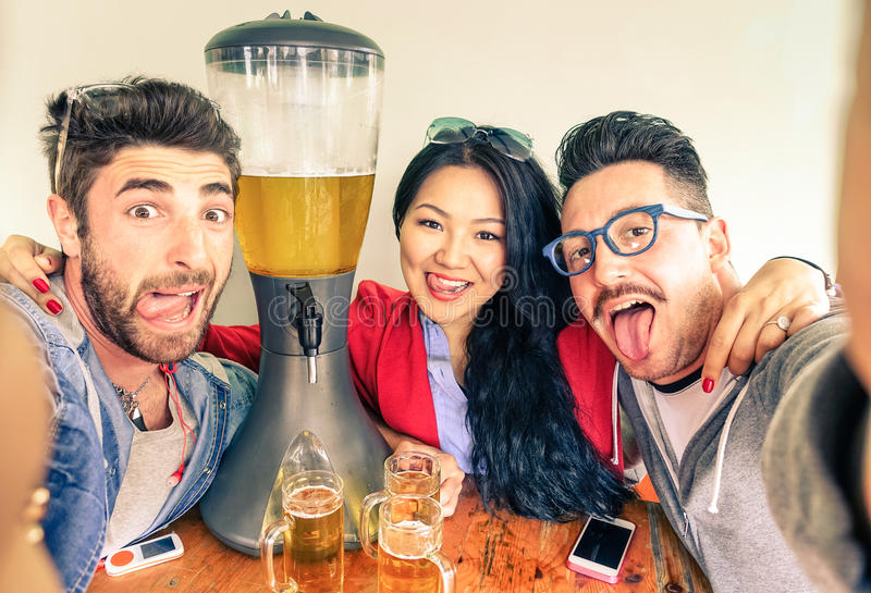 Happy friends taking selfie with funny tongue out and beer tower. Happy friends taking selfie with funny tongue out near beer tower dispenser - Concept of stock photos