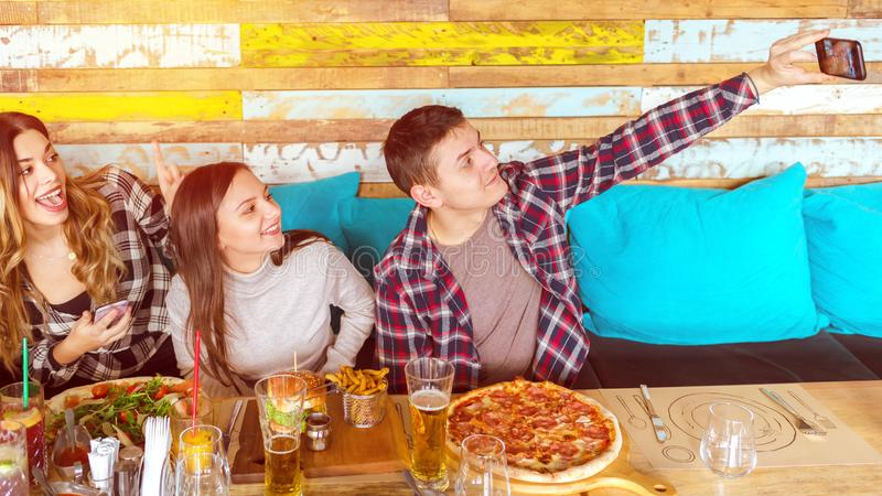 Happy friends taking selfie at lunch party eating pizza and hamburgers with fries stock photo