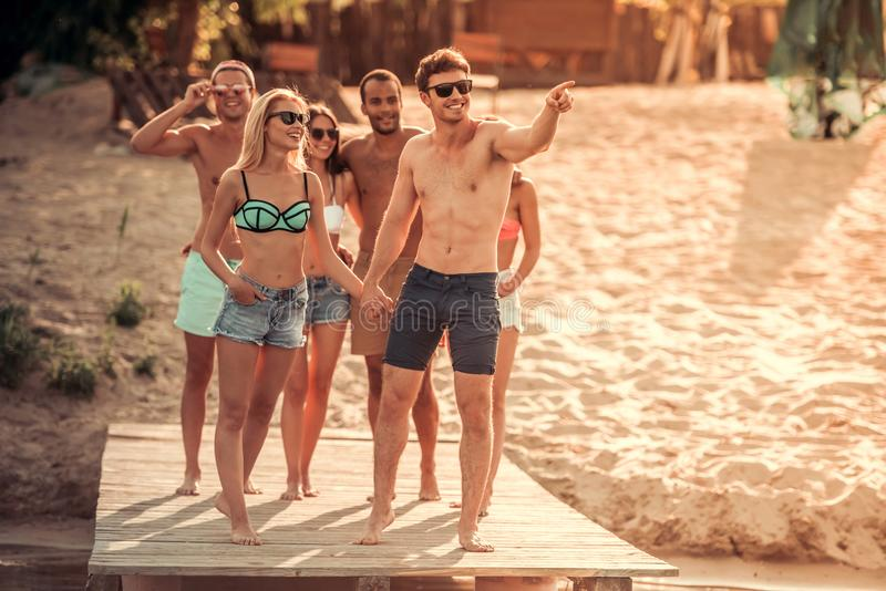 Friends on the sea. Happy friends are talking and smiling while walking along the pier at the sea stock photography