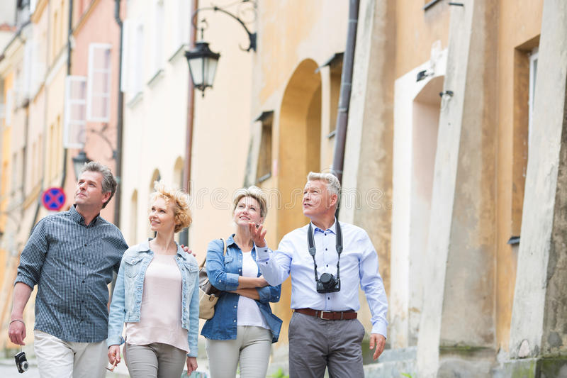 Happy friends talking while walking in city royalty free stock photography
