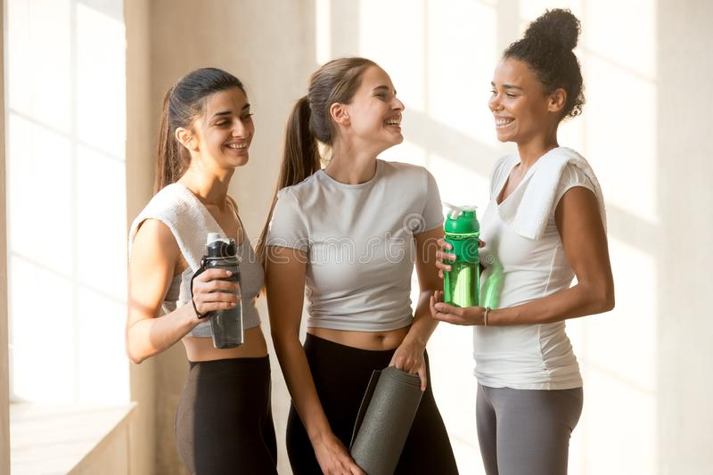 Happy friends talking after yoga session at gym. Indian mixed race caucasian beautiful diverse friends standing together talking relaxing after yoga session royalty free stock photo