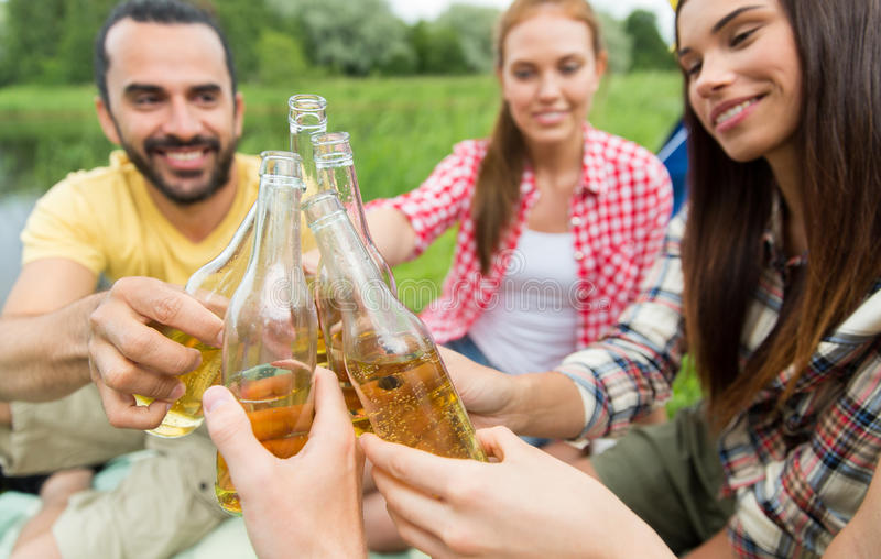 Happy friends with tent and drinks at campsite. Camping, travel, tourism, hike and people concept - happy friends clinking glass bottles and drinking cider or stock photo