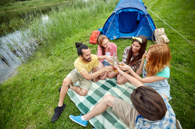 Happy friends with tent and drinks at campsite. Camping, travel, tourism, hike and people concept - happy friends with glass bottles drinking cider or beer at royalty free stock images