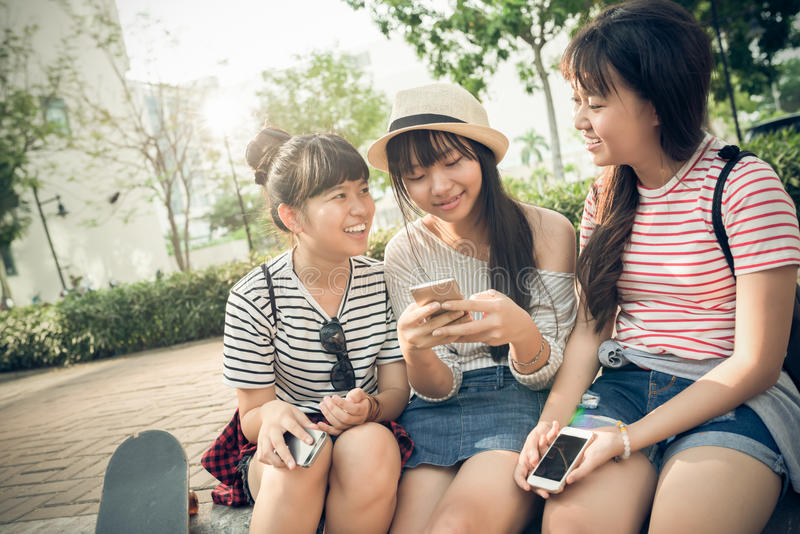 Happy friends. Three Vietnamese schoolgirls having fun together outdoors royalty free stock photo