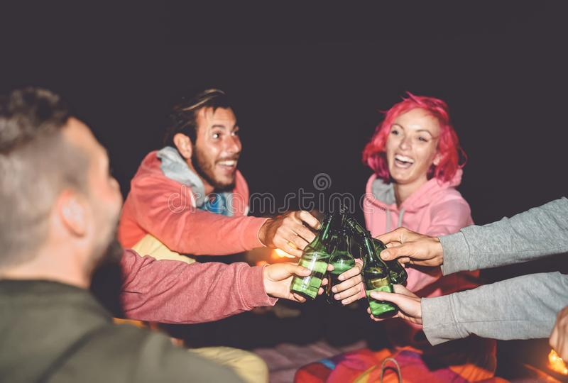 Happy friends toasting beers while camping outdoor - Group young people having fun making party together. Millennial generation and youth lifestyle culture royalty free stock images