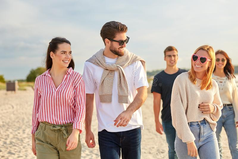 Happy friends walking along summer beach royalty free stock photography