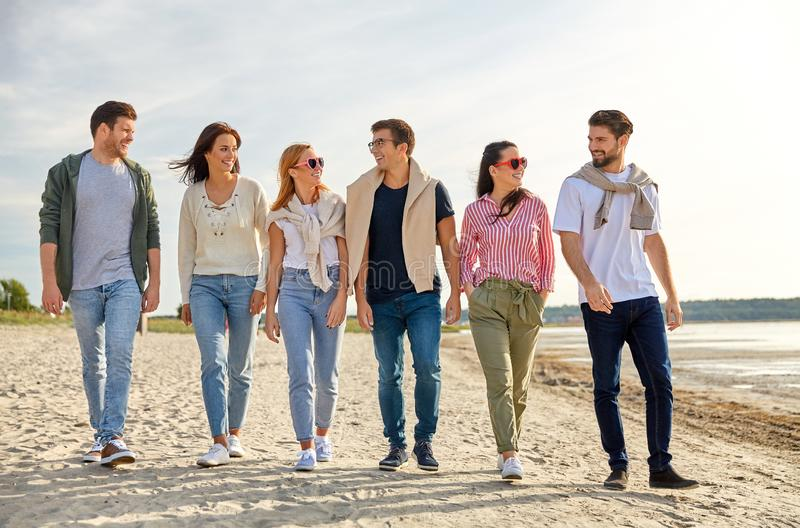Happy friends walking along summer beach royalty free stock photo