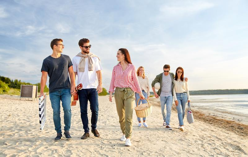 Happy friends walking along summer beach stock photography