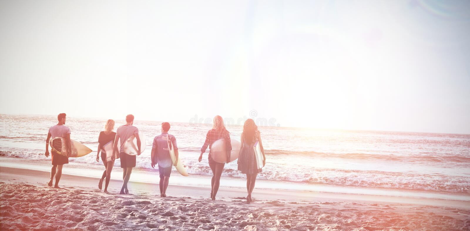 Happy friends walking with surfboards stock images