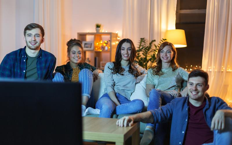 Happy friends watching tv at home in evening stock photos