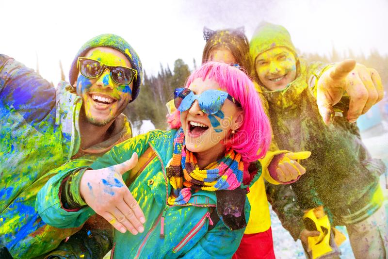 Happy friends at winter holi colors festival royalty free stock photography