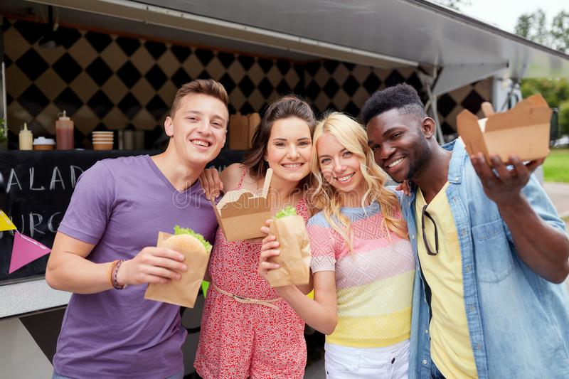 Happy friends with wok and burger at food truck stock photography