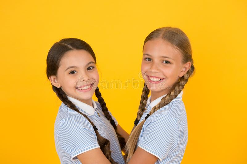 Happy friends on yellow background. fashion beauty. childhood happiness. sisterhood concept. small girls in retro school. Uniform. children in vintage style stock photo