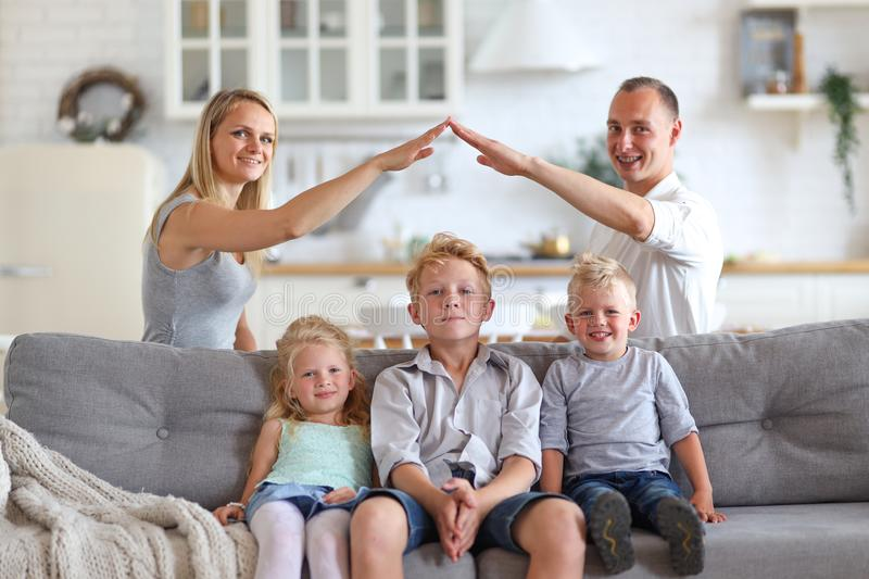 Happy full family with three kids sitting on sofa, mom and dad making roof figure with hands arms over heads. New stock images