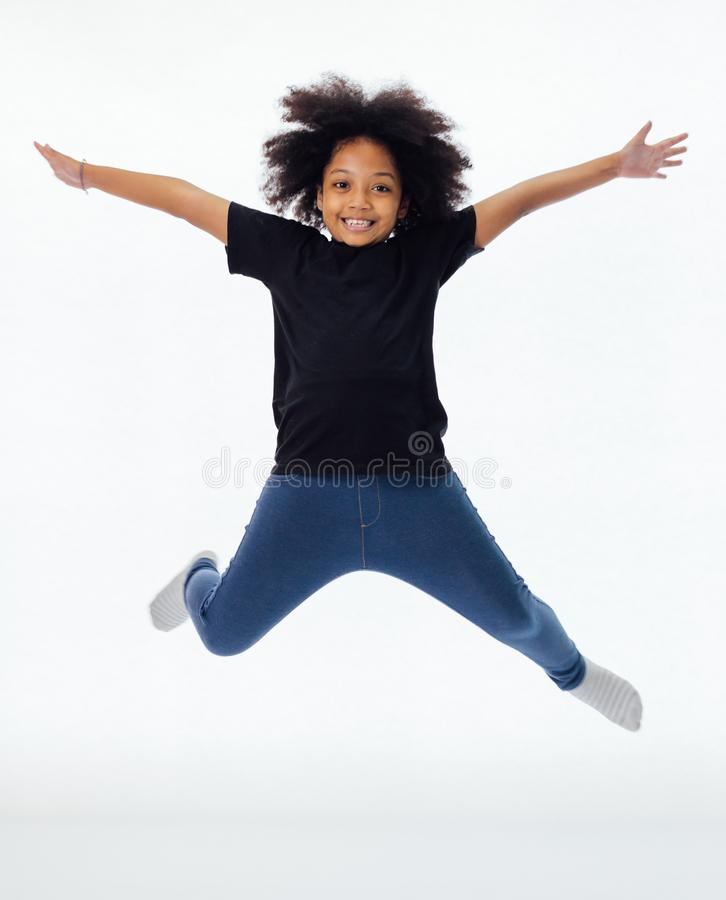 Happy and fun African American black kid jumping with hands raised isolated over white background. stock image