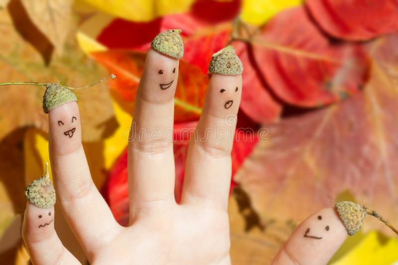 Happy fun autumn acorn family against colorful leaves fall background concept stock photography