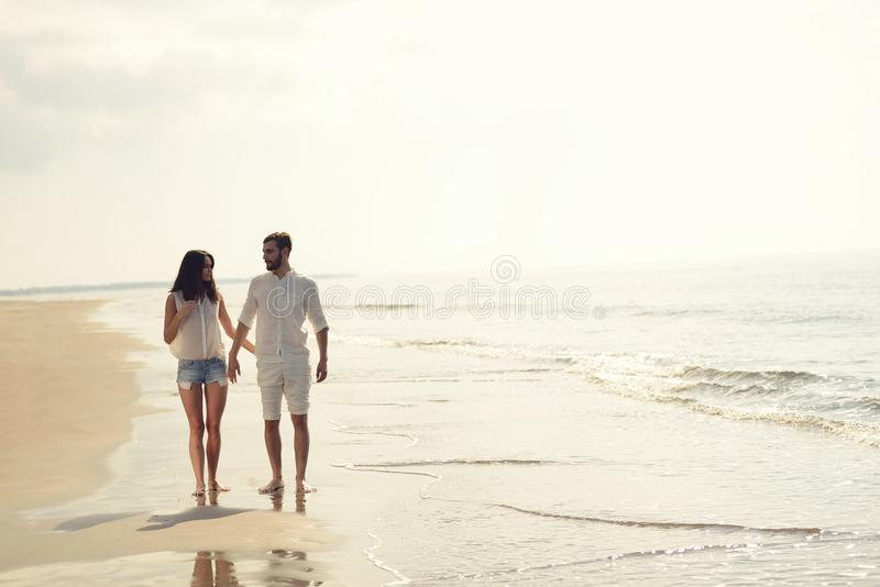 Happy fun beach vacations couple walking together laughing having fun on travel destination. Beach summer vacation couple running on holidays. Happy fun beach royalty free stock photography