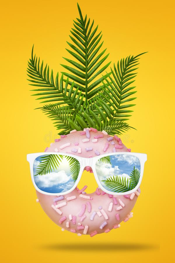 Happy fun face made of pink donut with sunglasses, green tropical leaves palm on bright pastel yellow and orange stock photo