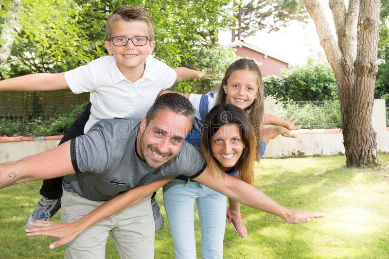 Fun family make piggyback in garden young father pretty mother glasses son and cute daughter in home park stock photos