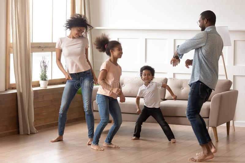 Happy funny active african family of four dancing at home. Happy funny active african american family of four parents and cute little mixed race kids dancing royalty free stock image