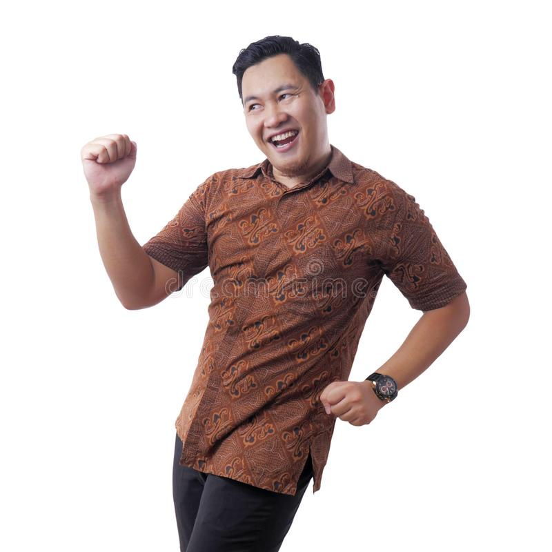 Happy Funny Asian Man Wearing Indonesian Batik Dancing Full of Joy royalty free stock photo